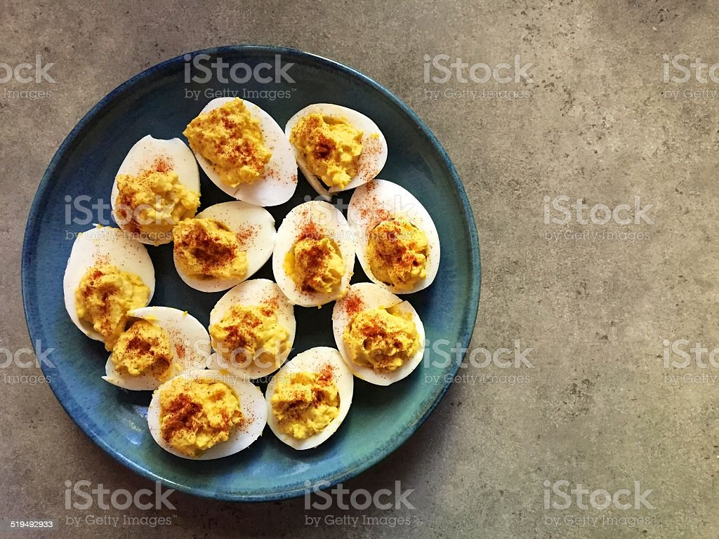 Devilled eggs on blue plate and grey background stock photo