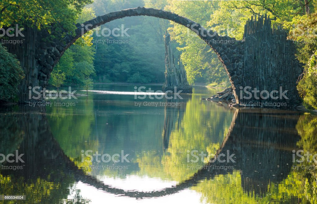 Devil's bridge in the park Kromlau, Germany,Flowering rhododendrons stock photo