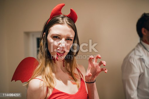 Woman dressed in a devil's outfit for Halloween looking at the camera pulling a face and making a claw with her hand.