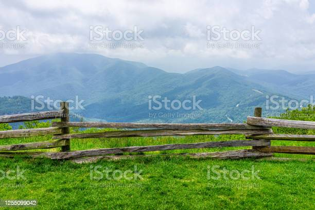Photo of Devil's Knob Overlook green grass field meadow and fence at Wintergreen resort town village near Blue Ridge parkway mountains in summer clouds mist fog covering rolling hills