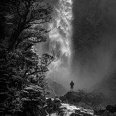 Man stands in awe in front of Devil's Punchbowl waterfall, Arthur's Pass N.P., New Zealand.