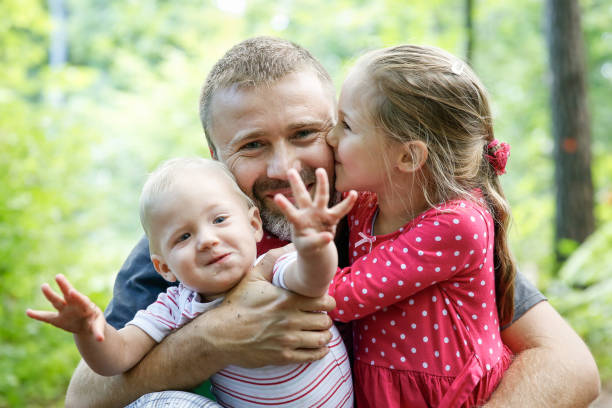 devoted father hugging his son and daughter, enjoying the outdoor. - fathers day stock pictures, royalty-free photos & images