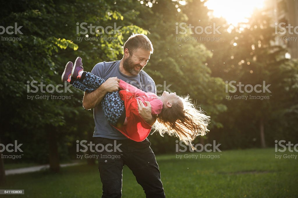 Devoted father spinning his daughter in circles stock photo