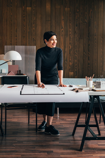 A successful female architect working on an architectural plan