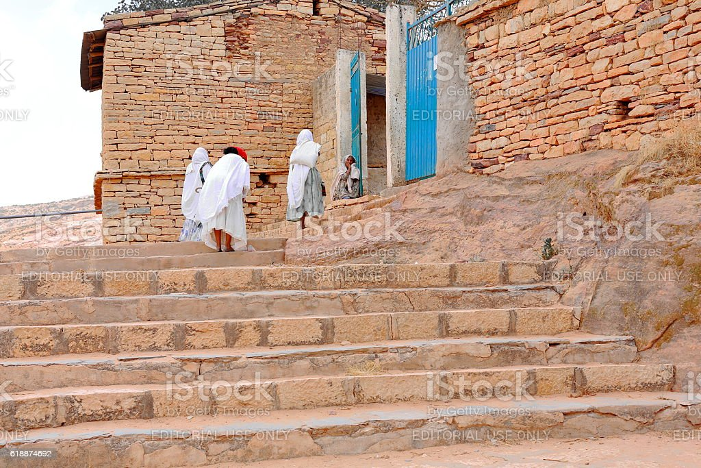 Devotee women climbing to Wukro Chirkos rock-hewn church. Wukro-Ethiopia. 0433 stock photo