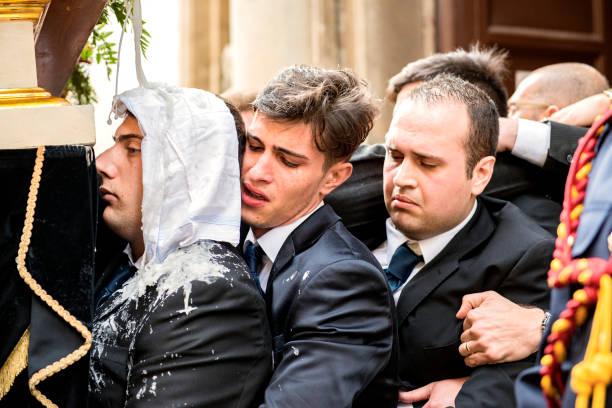 Anhänger während der via crucis tragen eine Statuengruppe als Wachstropfen auf ihrer Kleidung – Foto