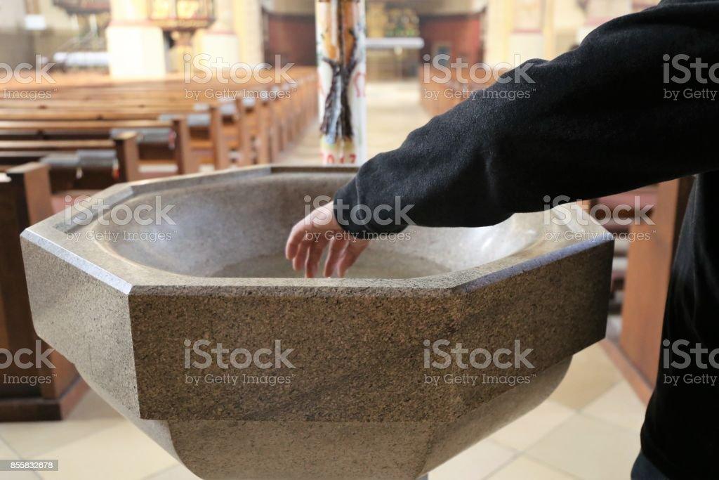 Frommer Christ seine Finger in heiliges Wasser eintauchen – Foto