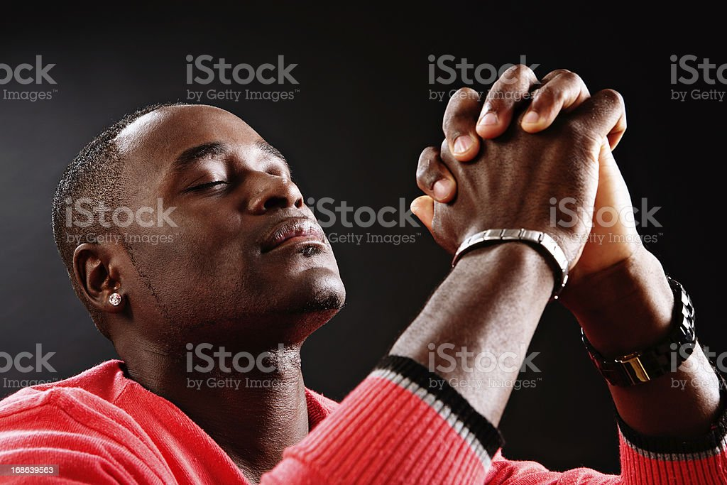 Devout young man prays fervently, eyes closed and hands clasped stock photo