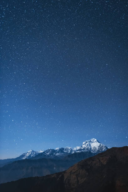 Dhaulagiri I night stars A view at night from Bayeli of Dhaulagiri I in the Nepal Himalayas at night. star field stock pictures, royalty-free photos & images