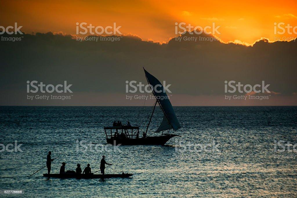 Dhow boat  and canoe in the sunset, Zanzibar stock photo