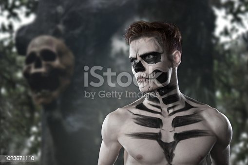 Dia de los Muerto Costume - Day of the dead is a mexican holiday. Here is a man with skull face and against the backdrop of the terrible forest and the dead