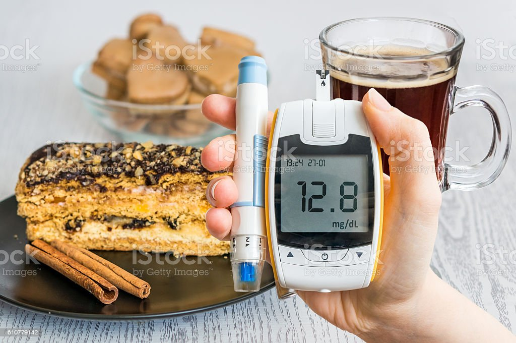 Diabetes and unhealthy eating. Hand holds glucometer. stock photo