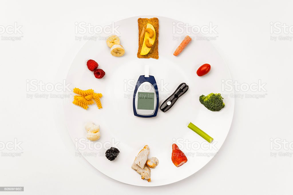 Diabetes clock concept with a glaucometer and food. stock photo