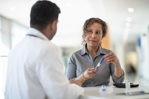 A woman discusses with her doctor about possibilities for diabetes treatment in a well lit medical facility.