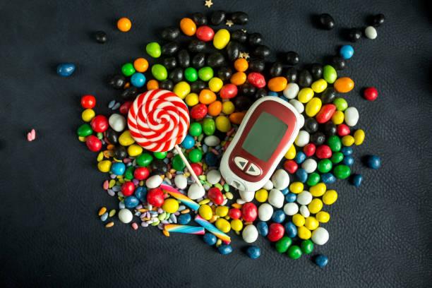 diabetes-krankheitskonzept. blutzuckermessgerät und hellen süßigkeiten. - hyperglycemia stock-fotos und bilder