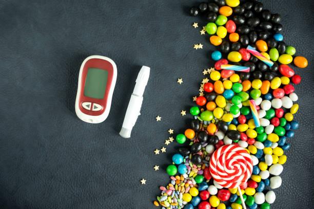 diabetes-krankheitskonzept. glucometer, lancet und hellen süßigkeiten. - hyperglycemia stock-fotos und bilder