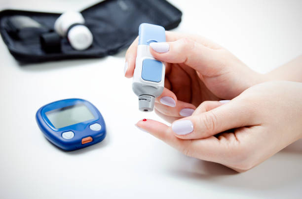 Diabetes doing blood glucose measurement. Diabetes doing blood glucose measurement. Woman using lancet and glucometer. lancet arch stock pictures, royalty-free photos & images
