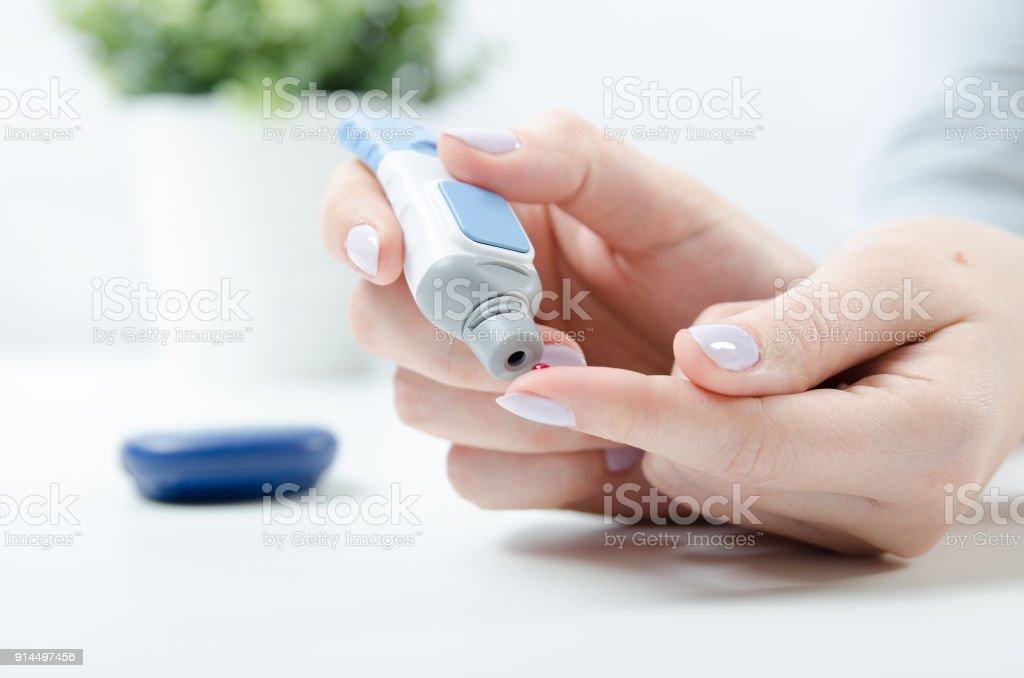 Diabetes doing blood glucose measurement. stock photo