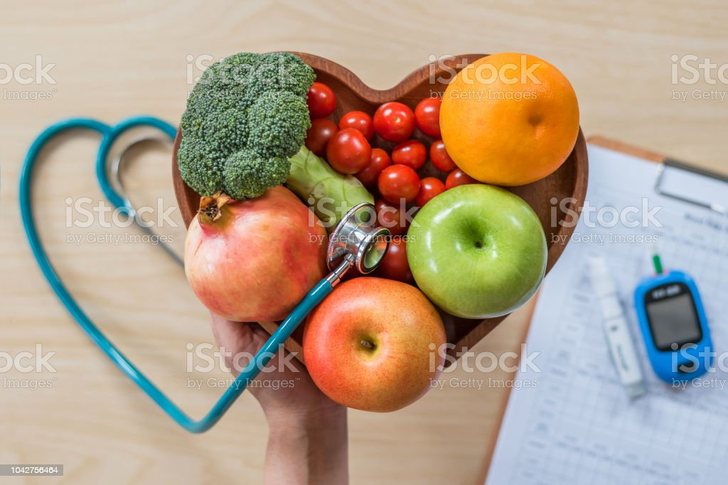 Diabetes monitor, Cholesterol diet and healthy food eating nutritional concept with clean fruits in nutritionist's heart dish and patient's blood sugar control record with diabetic measuring tool kit stock photo