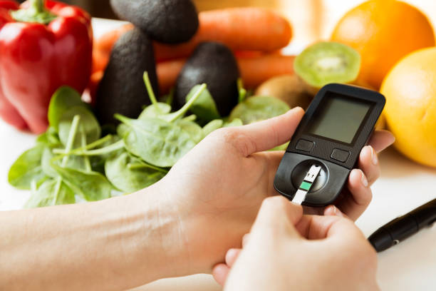 diabetes monitor, diet and healthy food eating nutritional concept with clean fruits and vegetables with diabetic measuring tool kit - diabetic stock photos and pictures