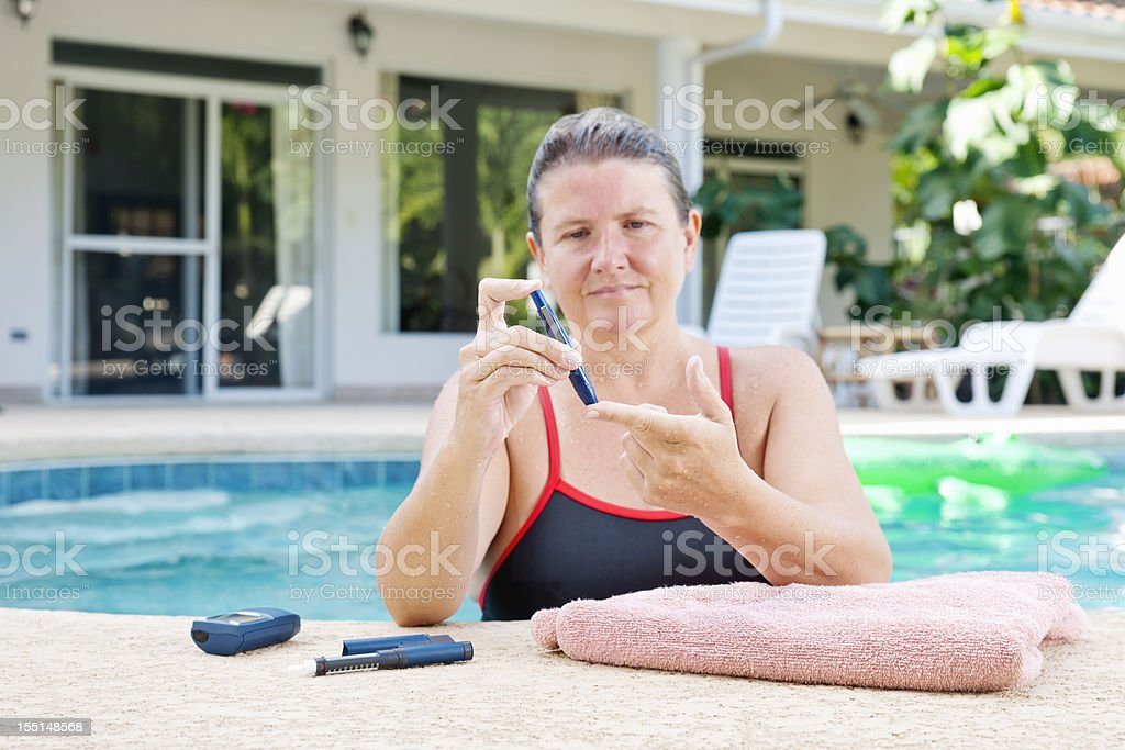 Diabetes patient checking her blood sugar before or after excercising stock photo
