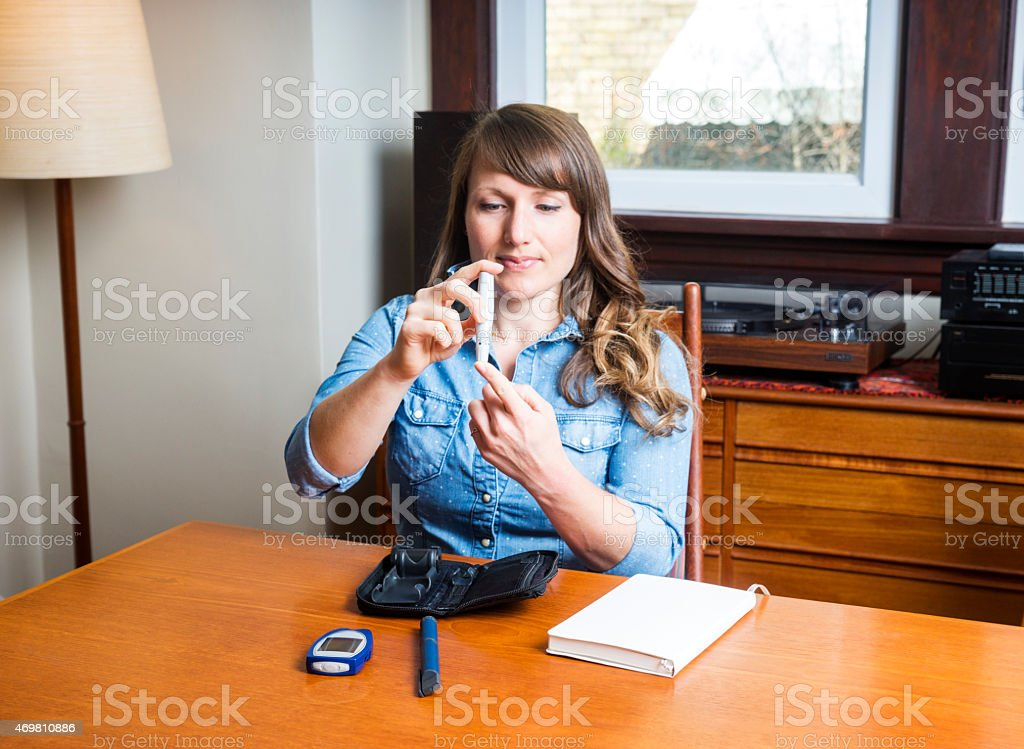 Diabetic 30s woman checking her blood sugar levels stock photo