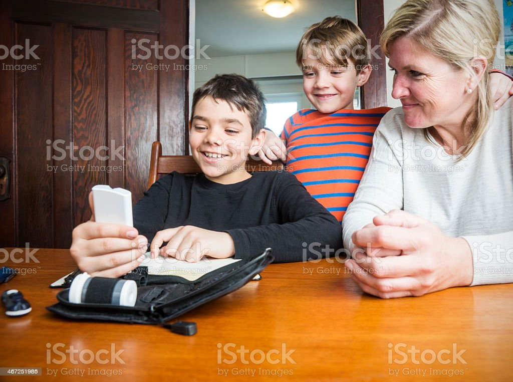 Diabetic child testing blood sugar with his family stock photo