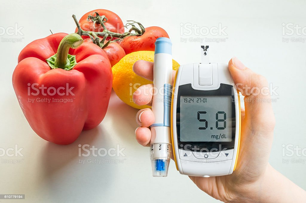 Diabetic diet, diabetes and healthy eating concept. Glucometer and vegetables. stock photo