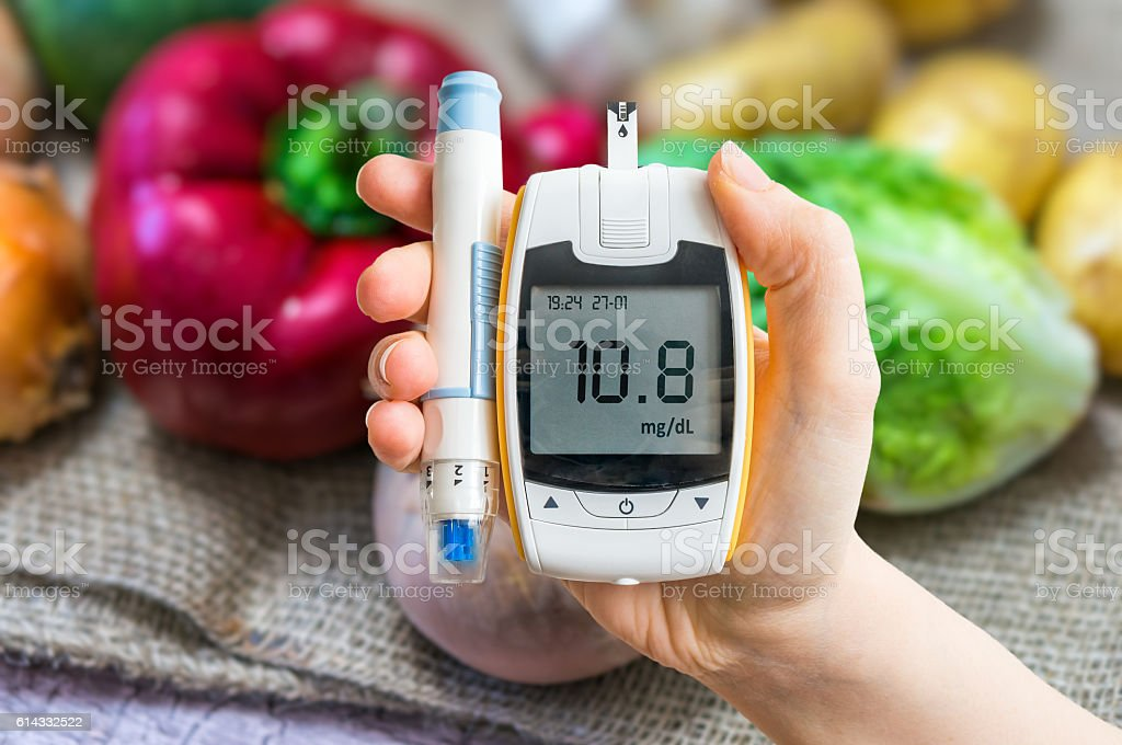 Diabetic diet, diabetes concept. Hand holds glucometer. Vegetables in background. stock photo
