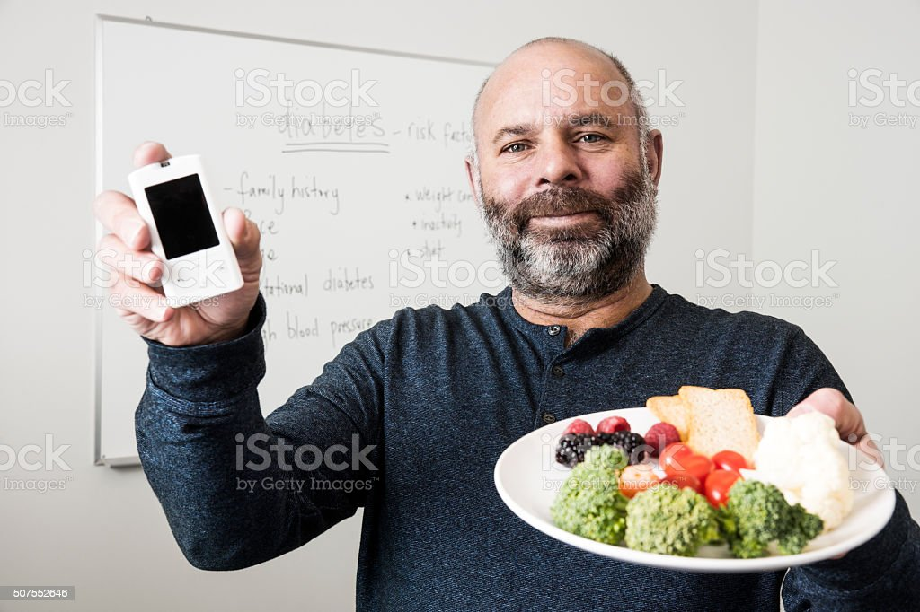 Diabetic man checking his blood sugar levels at work stock photo