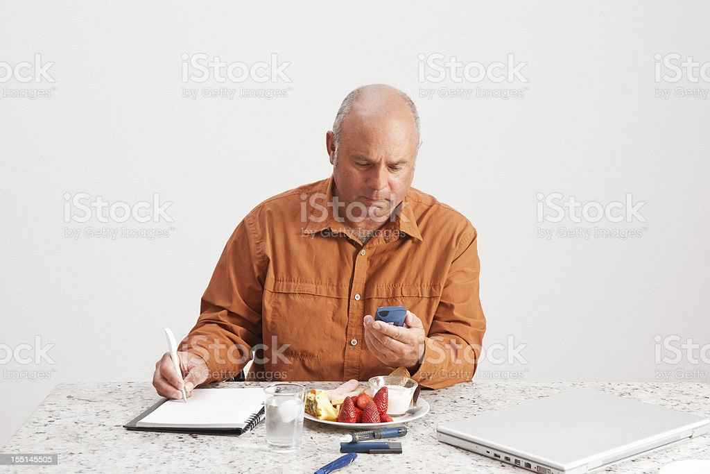 Diabetic man checking his levels stock photo