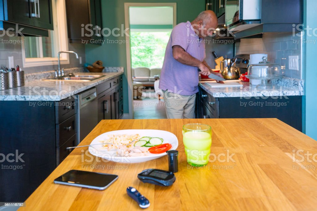 A diabetic mixed race man in his fifties preparing a meal with blood...