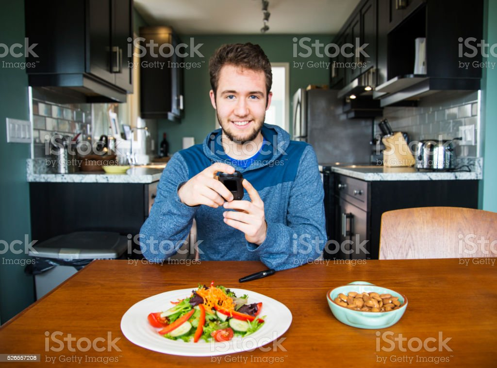 Diabetic man monitoring his blood sugar levels stock photo