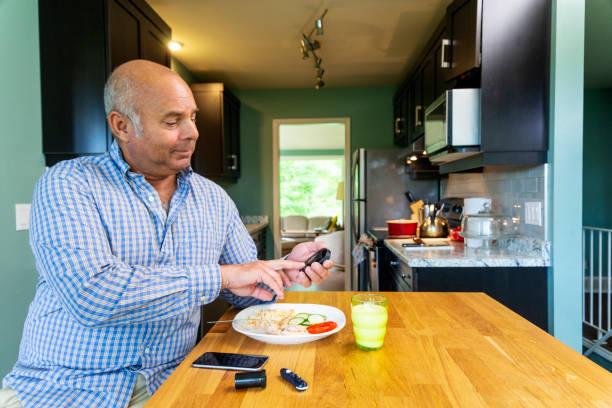 ein diabetiker mischlinge mann in den fünfzigern sein blutzuckerspiegel testen - fett nährstoff stock-fotos und bilder