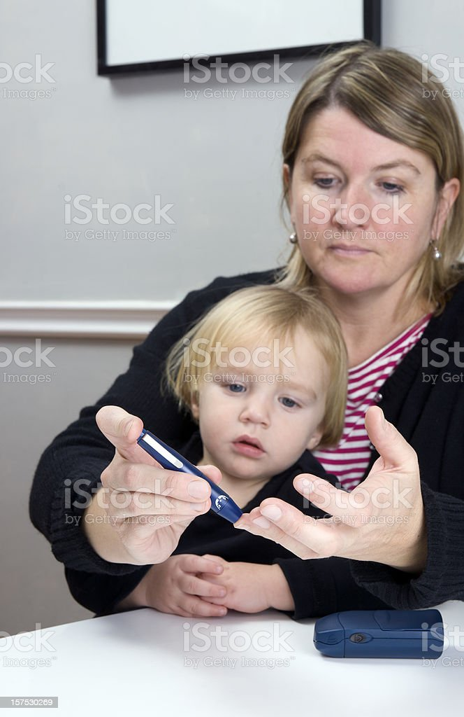 Diabetic mother with small child checking blood sugar stock photo