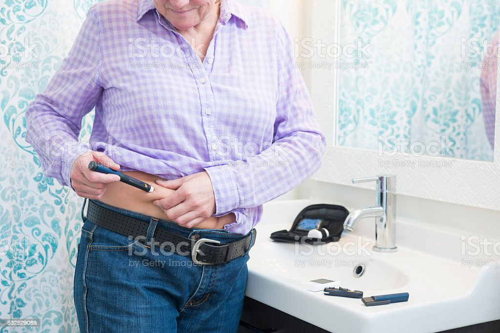 Diabetic patient injecting with insulin stock photo