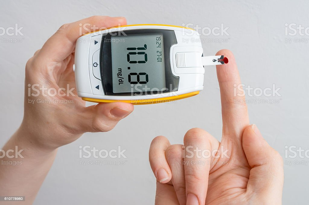 Diabetic patient is holding glocimeter and measuring glucose level. stock photo