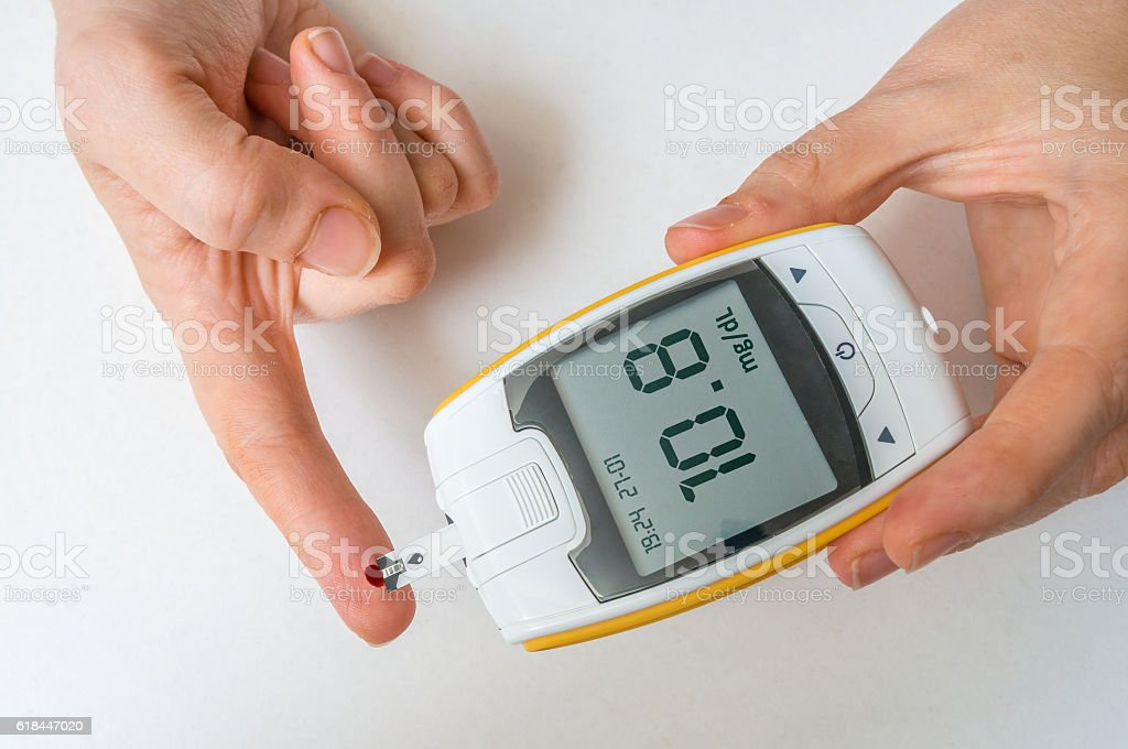 Diabetic patient is monitoring glucose level from blood from finger. stock photo