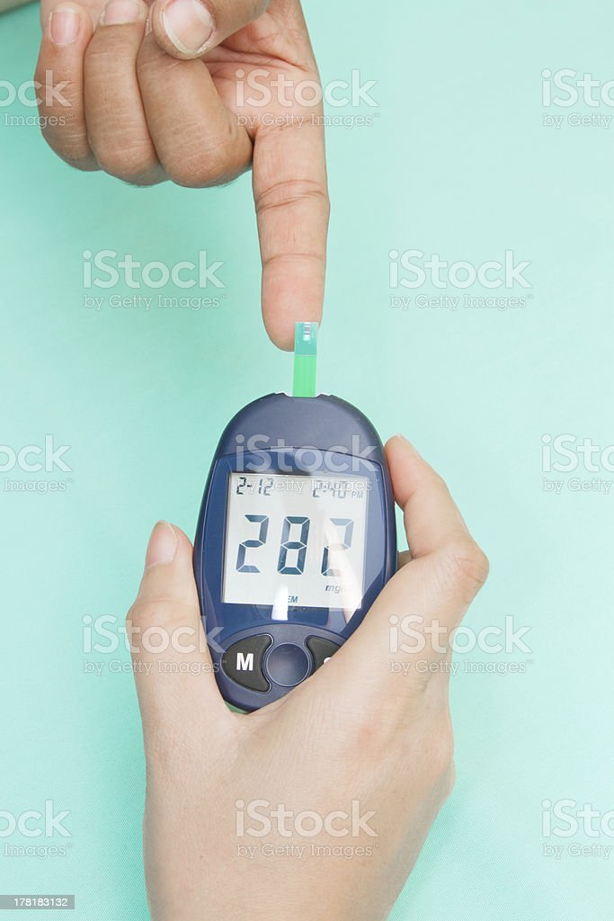 Diabetic patient measuring glucose with glucometer royalty-free stock photo