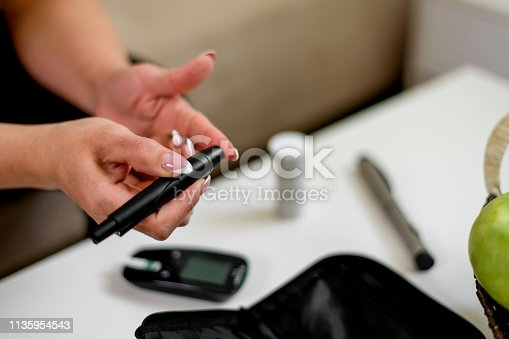 Diabetic patient testing her blood for sugar level
