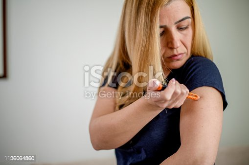 Diabetic person injecting insulin at home