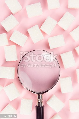 Sugar with magnifying glass on the pink background.