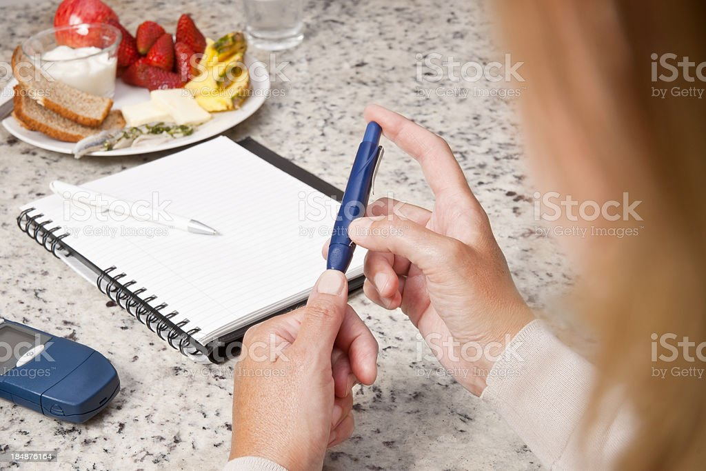 Diabetic woman checking her blood sugar levels royalty-free stock photo