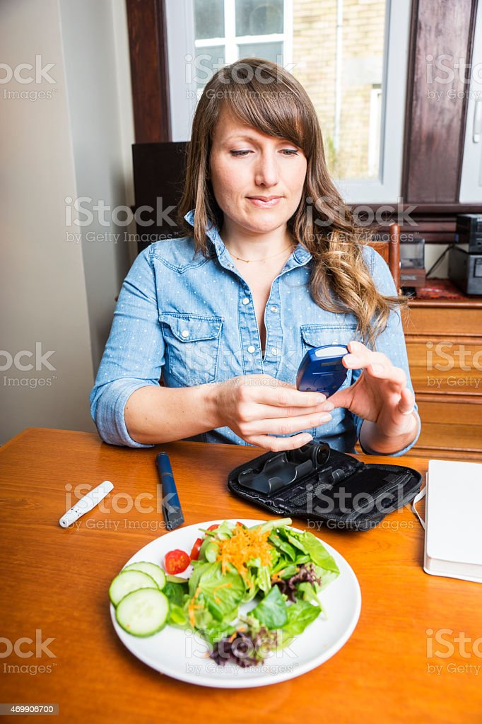 Diabetic woman in her 30s checking blood levels stock photo