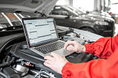 istock Diagnosing car engine with a laptop 1081594590