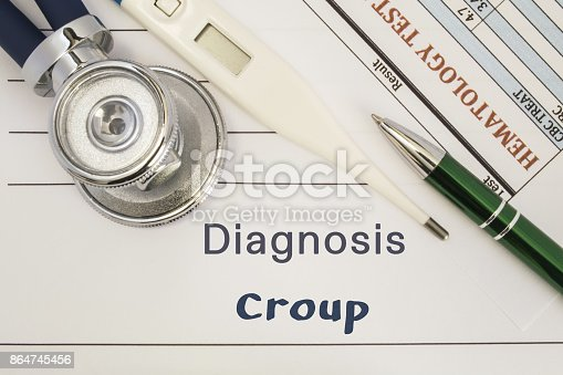 Diagnosis Croup. Stethoscope, electronic thermometer, patient blood test results lying on medical history, which is written diagnosis Croup. Concept for internal medicine, ENT