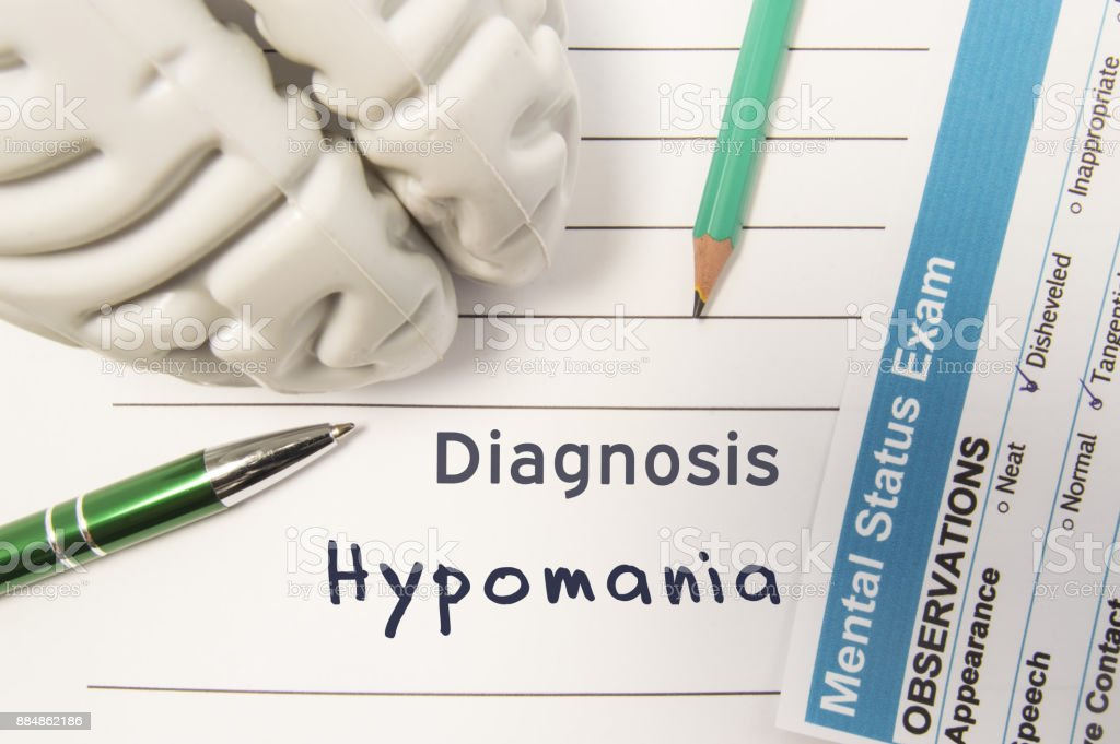 Diagnosis Hypomania. Figure of human brain, result of mental status exam, pen and pencil surrounded written psychiatric diagnosis Hypomania in medical report on doctors deck. Concept for psychiatry stock photo