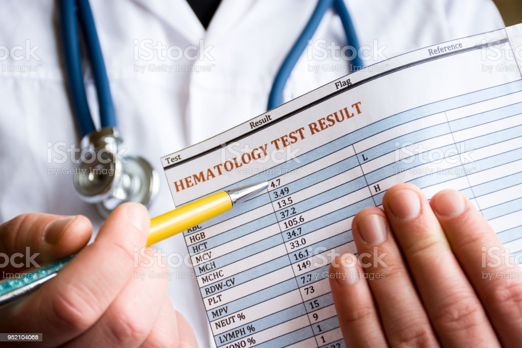 Diagnosis in hematology and hematological blood tests concept photo. Doctor holds in his hand result of blood test and indicates with pen in the other hand on the parameters and performance analysis stock photo