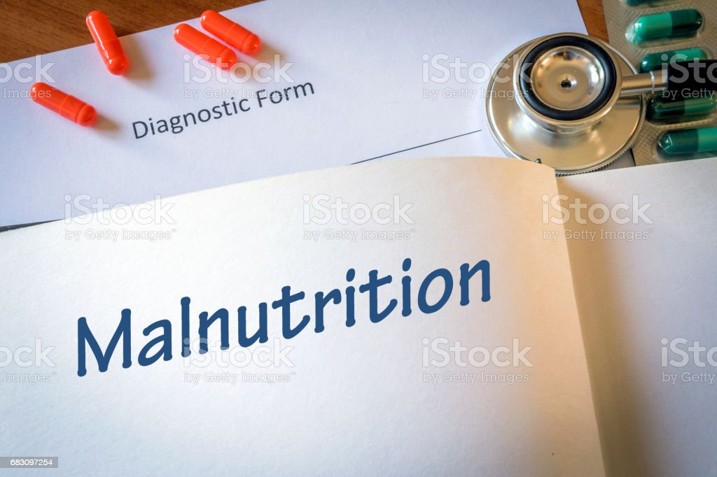Diagnosis malnutrition written in the diagnostic form and pills foto de stock royalty-free