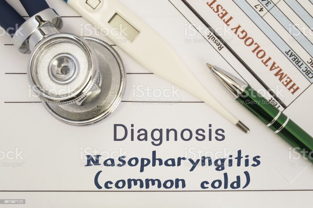 Diagnosis Nasopharyngitis (common cold). Stethoscope, electronic thermometer, patient blood test results lying on medical history, which is written diagnosis Nasopharyngitis (common cold) stock photo